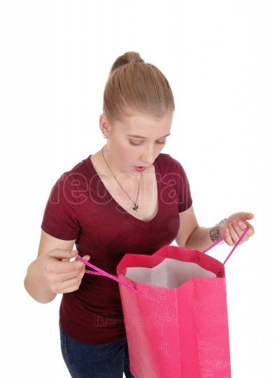 Woman looking into her empty shopping bag