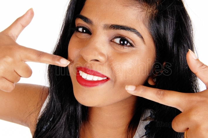 Woman pointing at her white teeth.