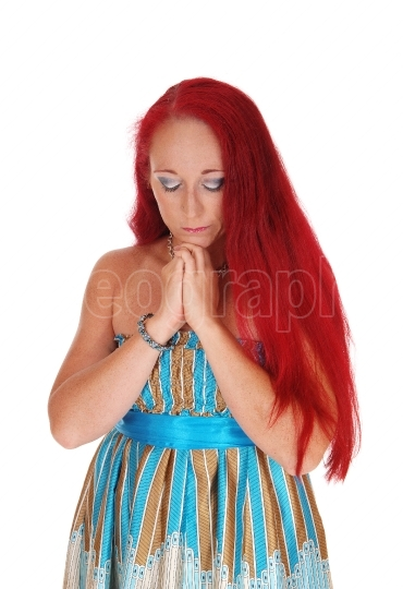 Woman praying with hands folded.