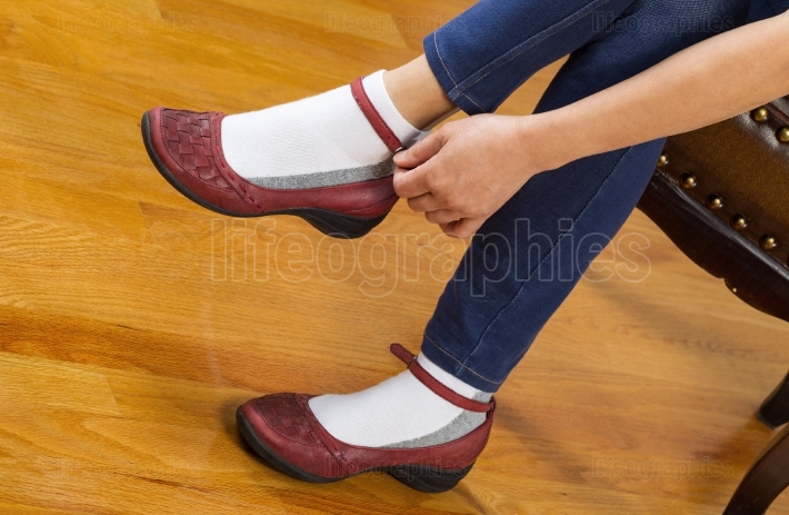 Woman putting on causal shoes while sitting on footstool at home