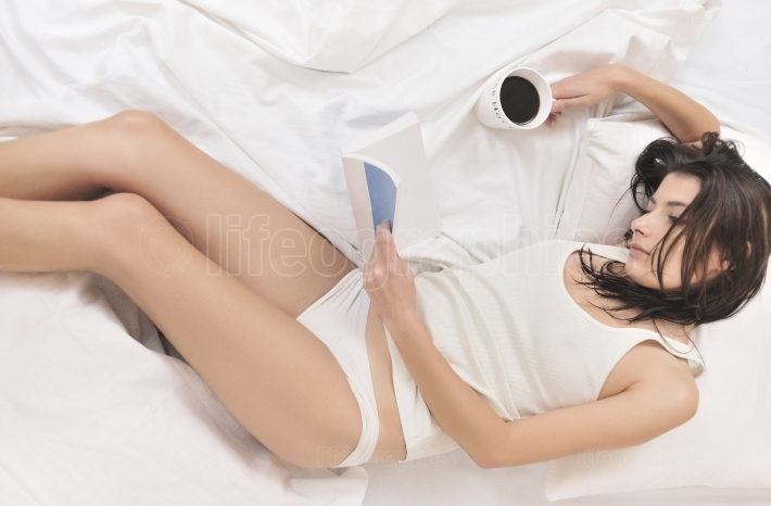 Woman reading in bed with a cup of coffee