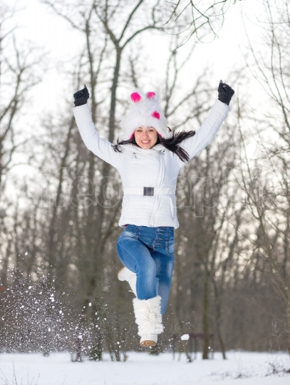 Woman runing in winter park very happy