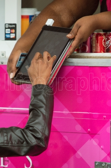 Woman signs digital tablet with finger in credit card transactio