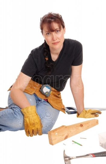 Woman sitting and working with tools.