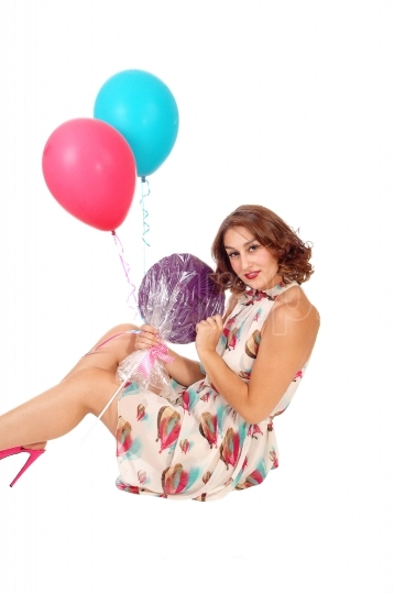 Woman sitting on floor with balloons.