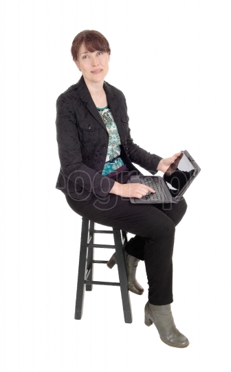 Woman sitting with a laptop on her lap.