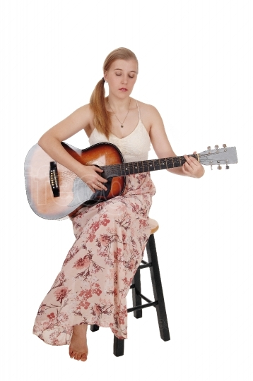 Woman sitting with her guitar and singing