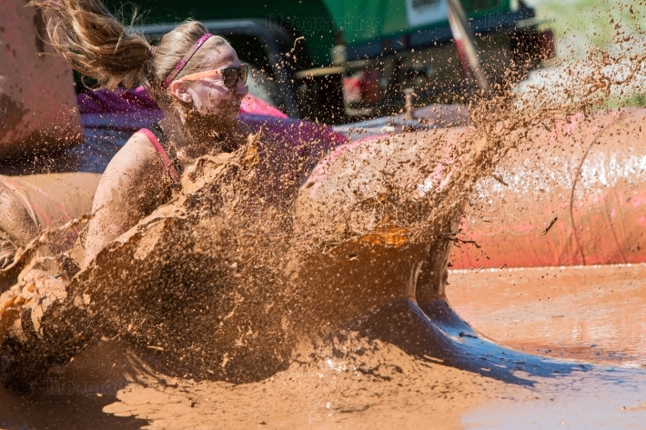 Woman splashes muddy water at dirty girl mud run event
