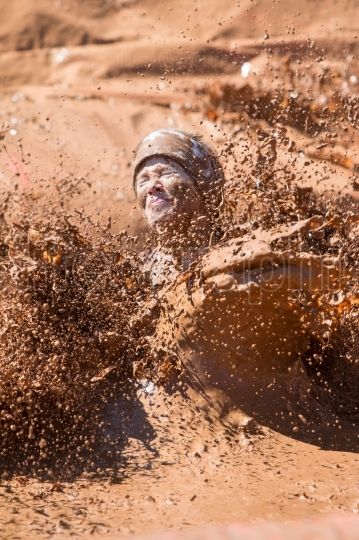 Woman splashes muddy water in dirty girl mud run