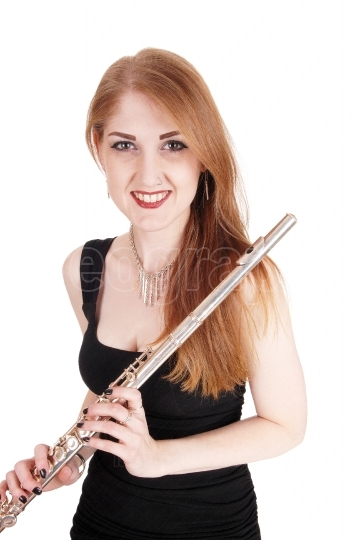 Woman standing, holding her flute and smiling