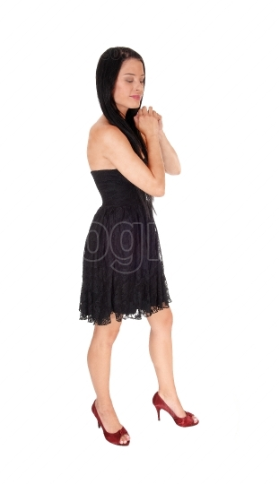 Woman standing in black dress praying with eyes closed