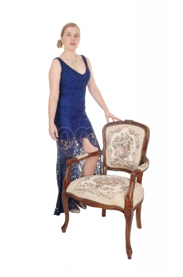 Woman standing in evening gown with armchair