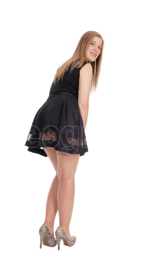 Woman standing in short black dress from back