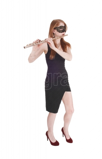 Woman standing, playing the flute wearing a mask