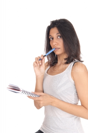 Woman standing with pen in her mouth