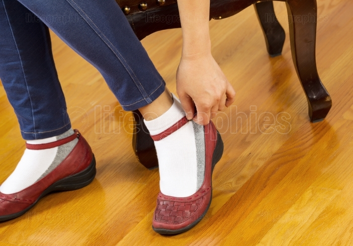 Woman Strapping on Shoes while sitting on home footstool