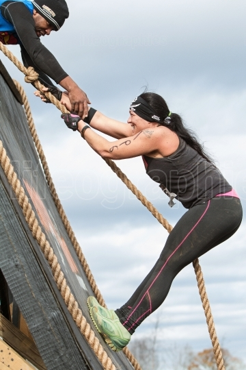 Woman struggles climbing wall in extreme obstacle course race