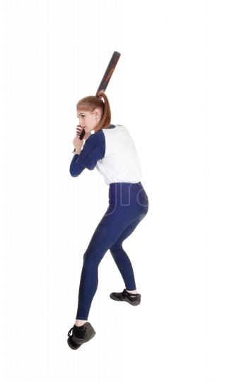 Woman swinging her bat in softball