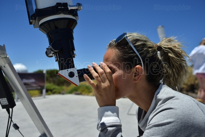 Woman tourist looking through big telescope