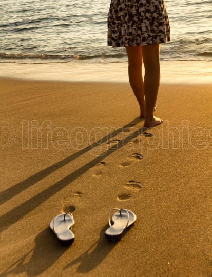 Woman walking on beach into ocean