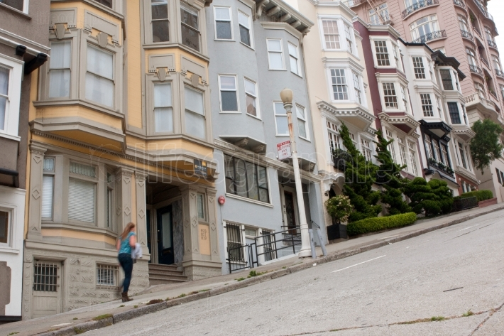 Woman walks up steep incline on nob hill street
