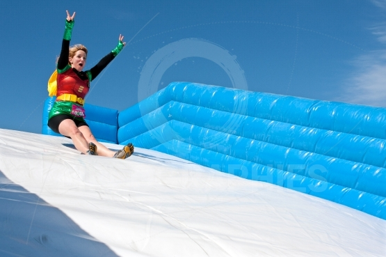 Woman Wearing Superhero Costume Goes Down Obstacle Race Slide