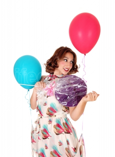 Woman with balloons and lollipop.