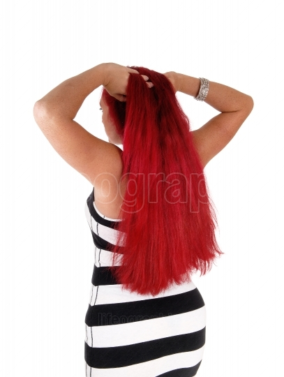 Woman with red hair standing from back.