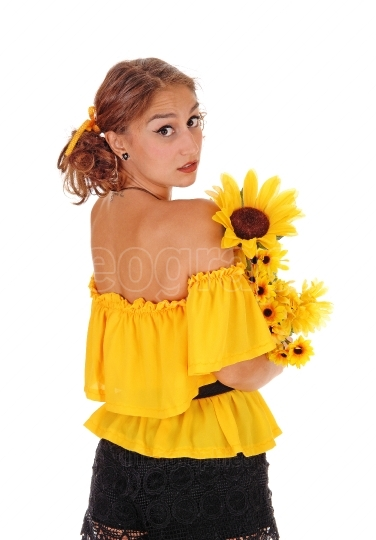 Woman with sunflowers looking over shoulder.