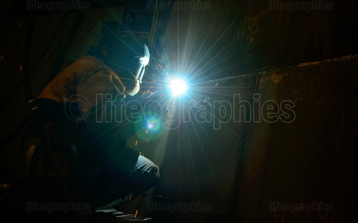 Woman worker welding