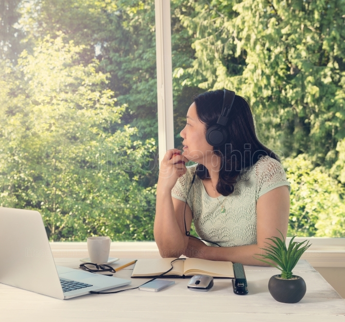 Woman working at home while looking out at bright daylight from