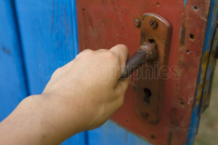 Woman's hand open old wooden door