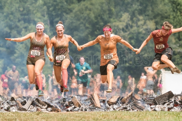 Women hurdle burning logs together in extreme obstacle course ra