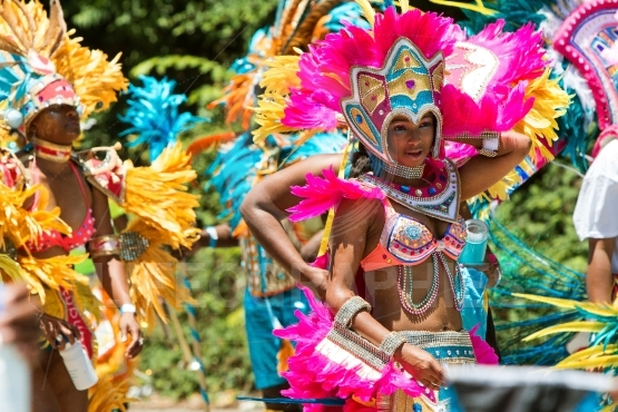 Women wearing costumes and feathered headdresses walk in caribbe