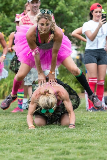 Women Wearing Tutus Play Leap Frog At Field Day Event