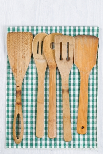 Wooden Cookware and cloth napkin on white wood