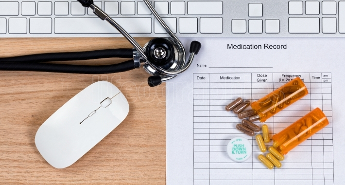 Wooden desktop with blank patient medication form plus capsules