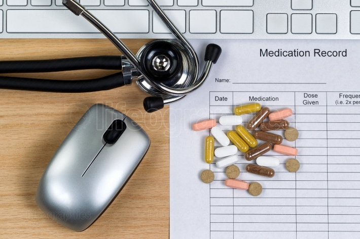Wooden desktop with patient medication form plus pills and equip