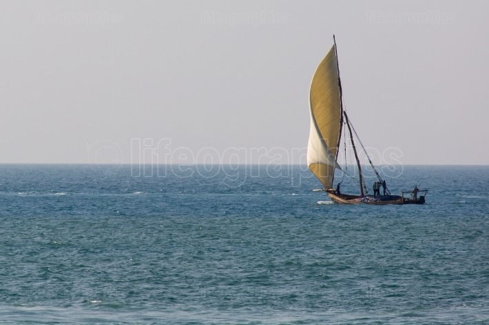 Wooden sailboat (dhow) on the clear turquoise water of Zanzibar