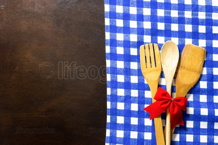 Wooden table with checked tablecloth and wooden kitchen utensils