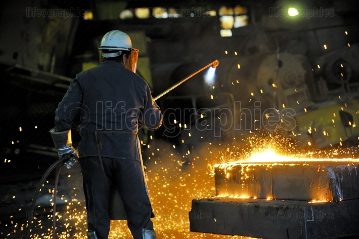 Worker using torch cutter