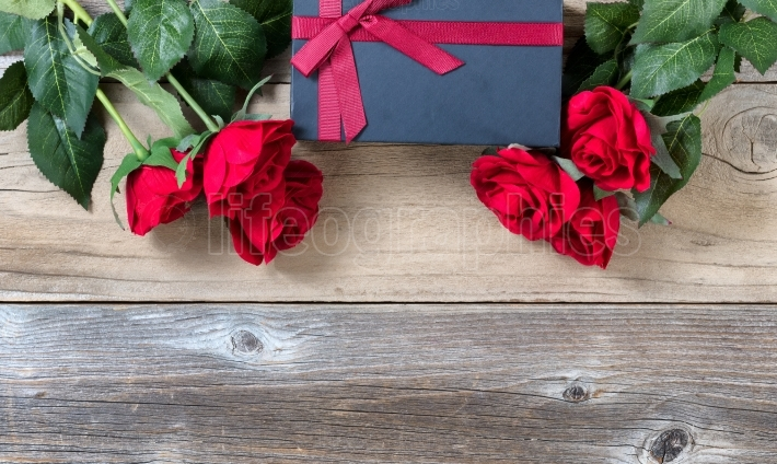 Wrapped Giftbox with lovely red roses on weathered wooden back