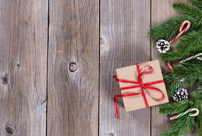 Xmas holiday wooden background with fir branches and gift box