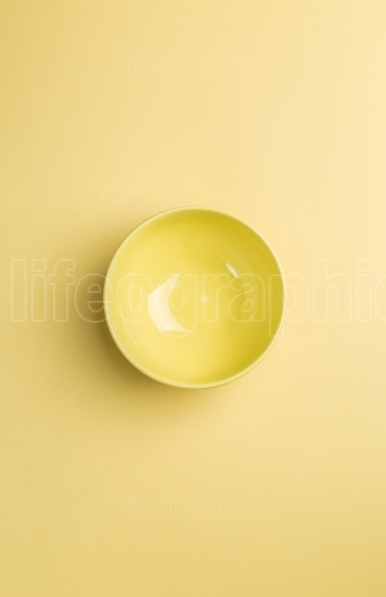 Yellow bowl on yellow background above view.Useful as a food bac