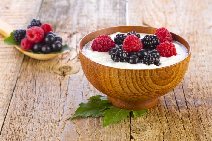 Yogurt with forest berries fruits in wooden bowl