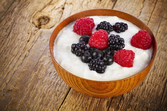 Yogurt with forest berries in wooden bowl