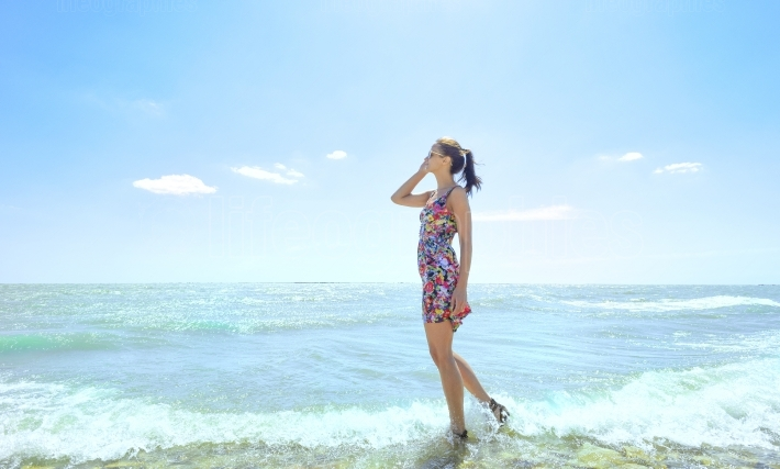 Young  woman standing in sea waves and holding her glasses