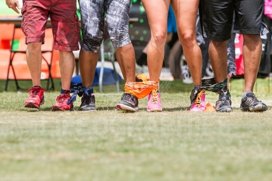 Young Adult Legs Walk In Unison At Five-Legged Race