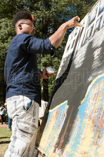 Young artist paints with his fingers at atlanta arts festival
