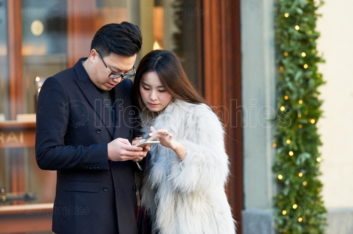 Young asian couple lookin in a phon